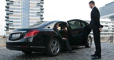Cgauffeur mit Fahrgast am Auto
